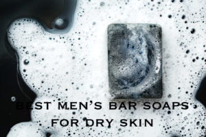 Black charcoal bar of soap in foam on dark background. Close-up composition. Top view. With text reading best men's bar soaps for dry skin