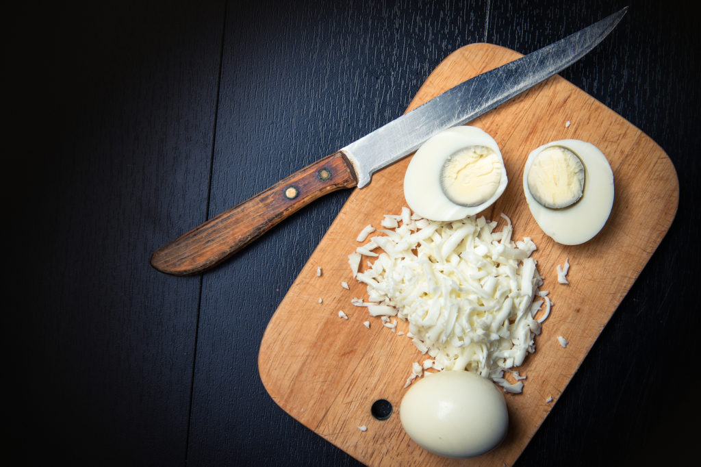 Knife on cutting board with an egg cut in half