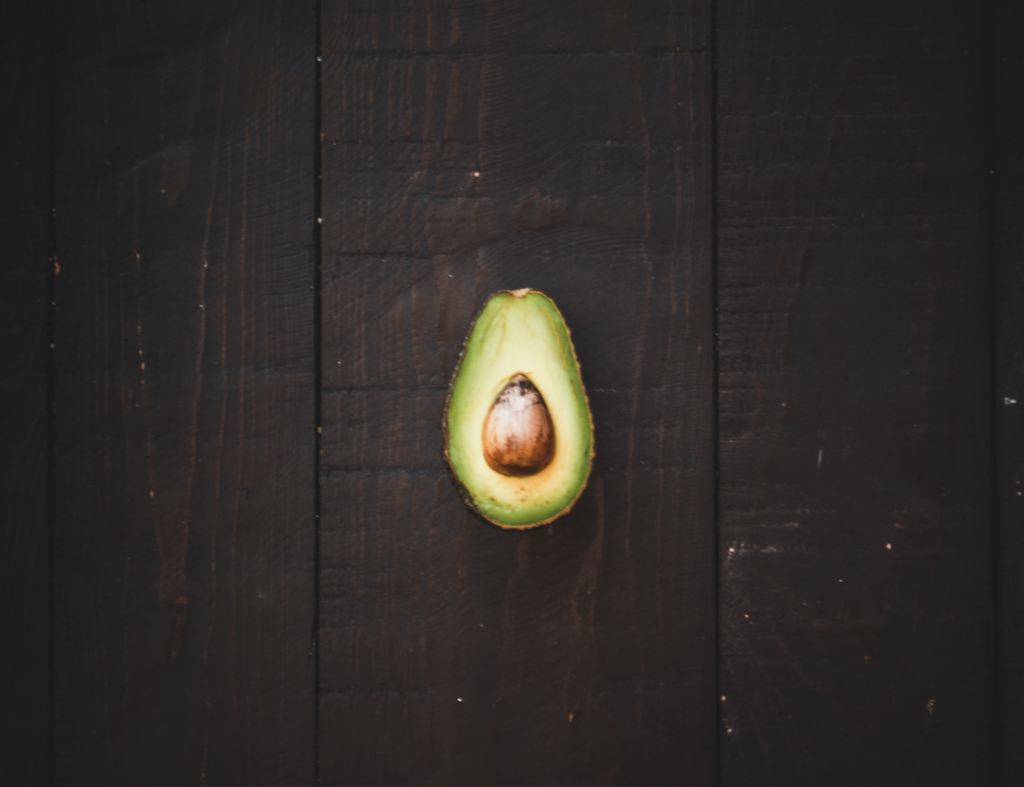 Cut avocado on wooden background