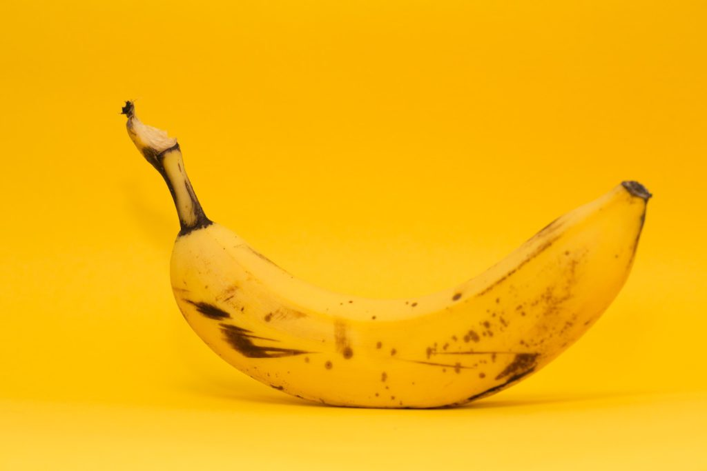 single banana on a yellow background