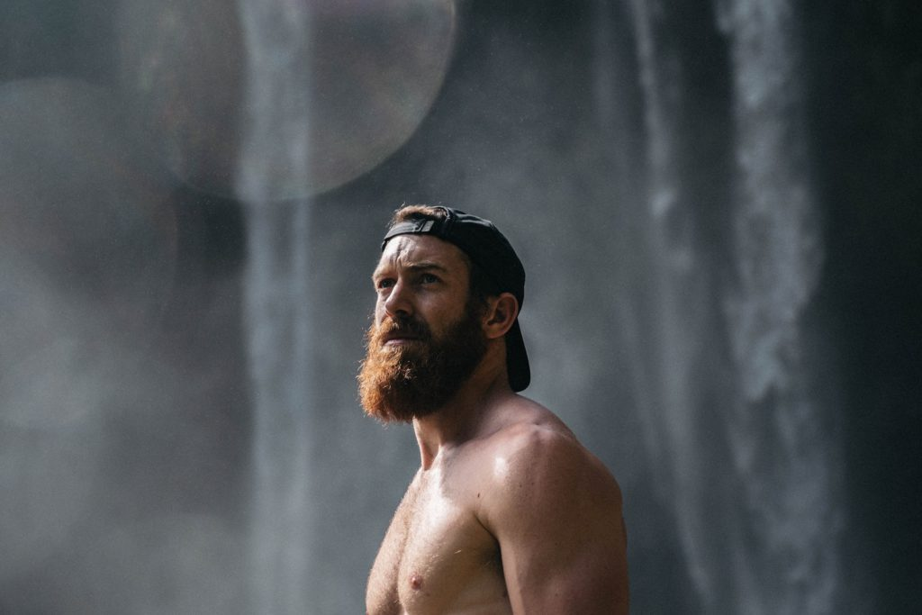 Man with a beard standing next to a waterfall