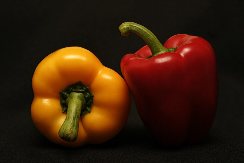 red and yellow bell peppers on a black background