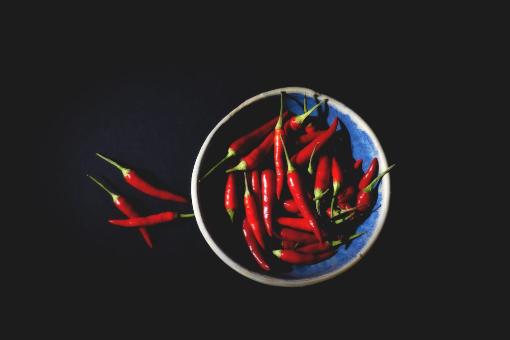 Bowl of red chili peppers on black background