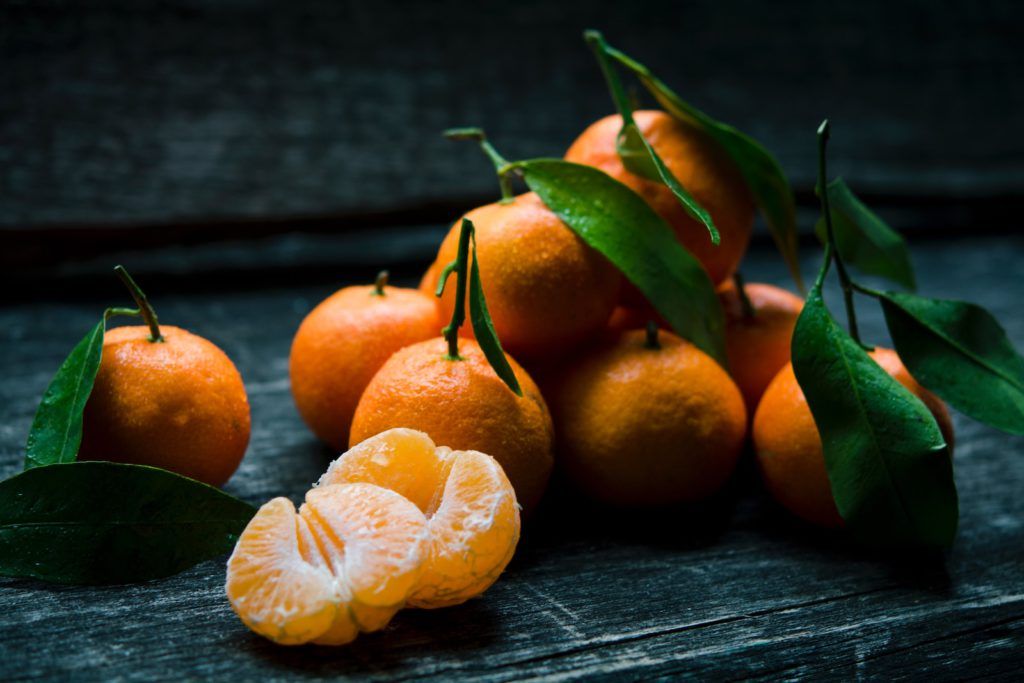 a bunch of mandarin oranges on a wooden surface