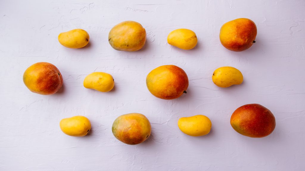 assorted sizes of mangoes on a white surface