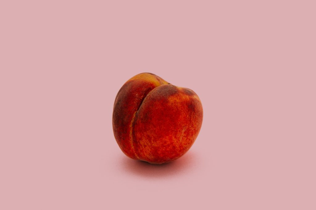 single peach on a pink background