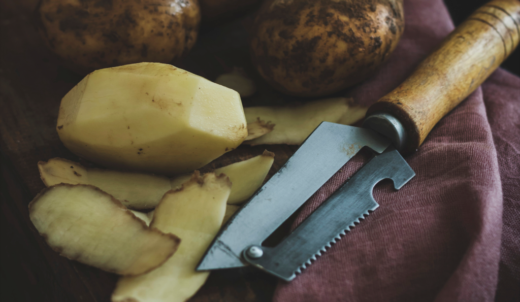 Peeled russet potato next to a peeler