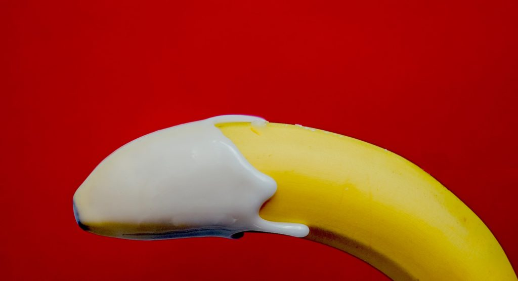 A single yellow banana with white cream on the tip against a red background