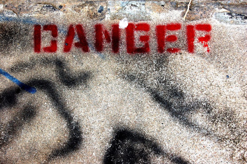 The word DANGER spray painted on the pavement.