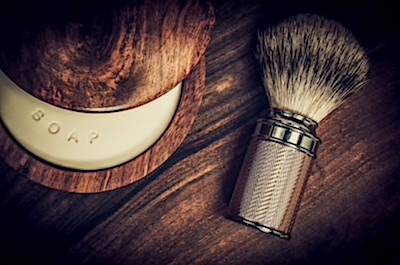 A bowl of shaving soap and a boar bristle brush