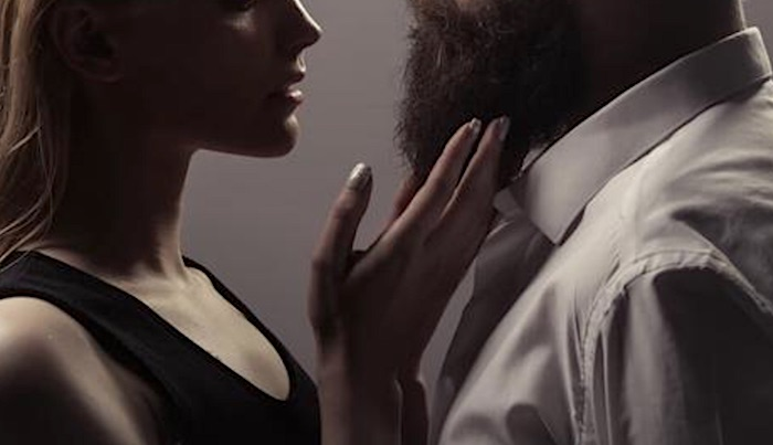 woman touching a man's beard
